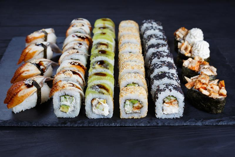 Sushi rolls, maki, nigiri and gunkan set served on black stone s stock photos