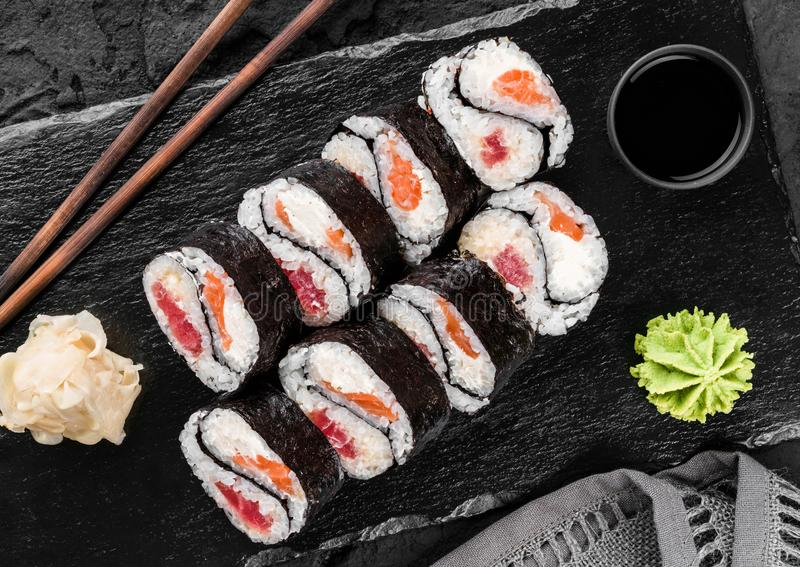 Sushi rolls and maki set with salmon and tuna fish, cheese and wasabi on black slate background. royalty free stock photo