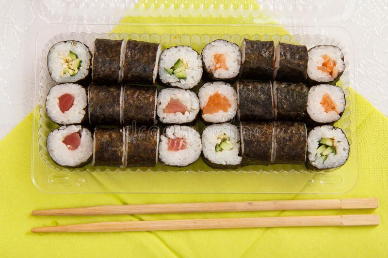 Sushi rolls in nori seaweed in plastic box with wooden sticks. Sushi rolls in nori seaweed sheets with avocado and red fish in plastic box with wooden sticks on royalty free stock images