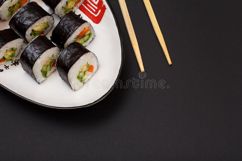 Sushi rolls in nori seaweed sheets on plate with wooden sticks on black background royalty free stock photography