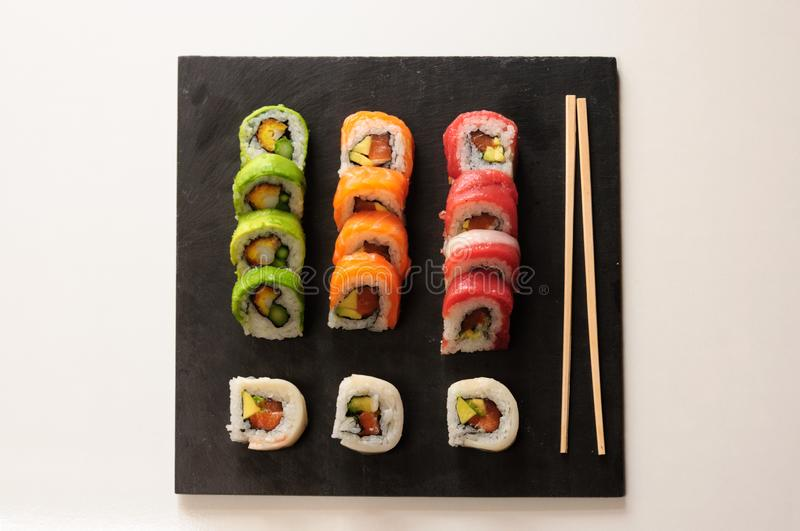 sushi rolls of red tuna, salmon, avocado and butter fish on slate dish. japanese food royalty free stock image