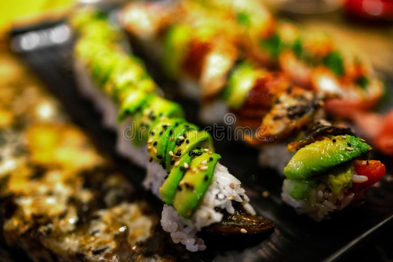 Sushi Rolls at restaurant. Luxury sushis with avocado and eel topping, rainbow maki, tuna, tobiko, sesame seeds. Japanese food royalty free stock photo