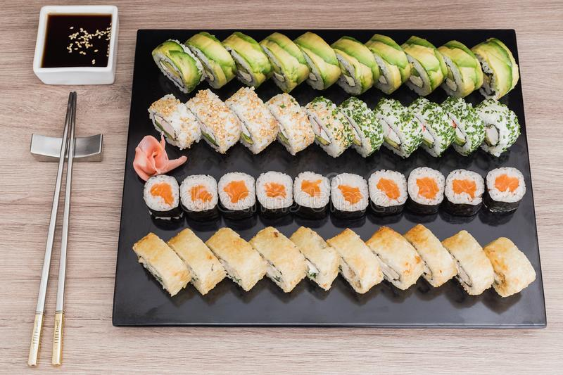 Sushi rolls, sake, california, tempura with soy sauce on a wooden table stock images