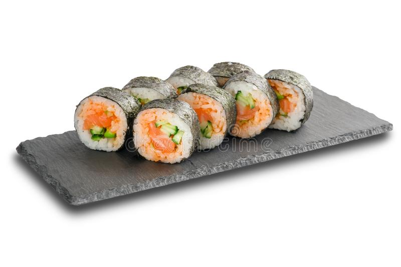 Sushi Rolls with salmon and cucumber wrapped in nori leaf on black slate or stone shale surface isolated on white. Background royalty free stock photography