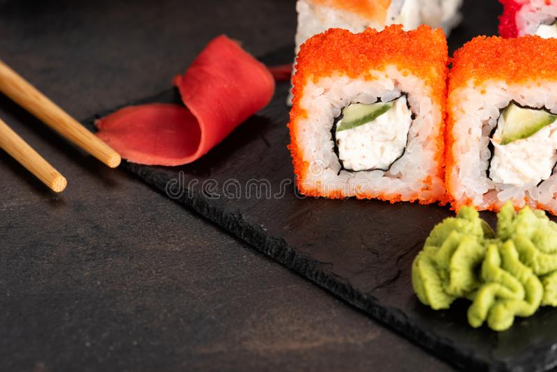 Sushi rolls and sashimi in a black stone plate stock images