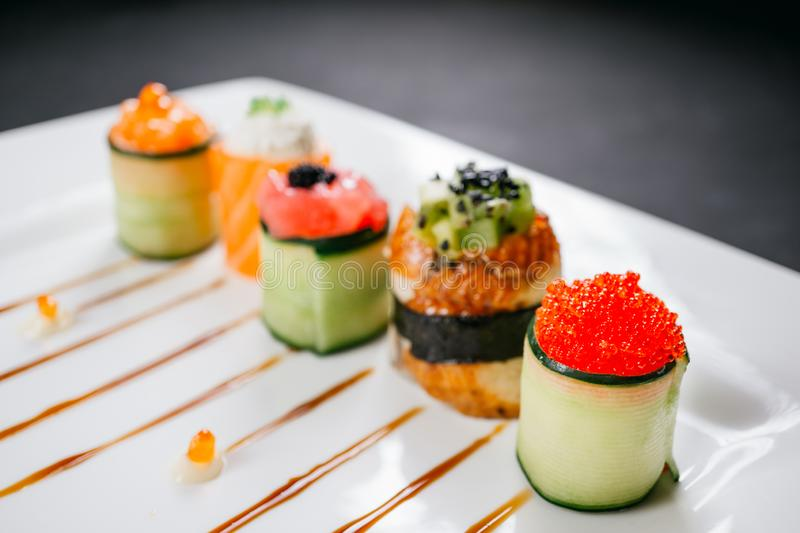 Sushi rolls set, fusion food style restaurant menu. Sushi rolls degustation, fusion food style restaurant menu, deluxe gastronomy. Set of finest seafood snacks royalty free stock image