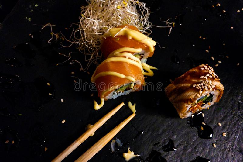 Sushi rolls set served on black stone slate on dark background stock image