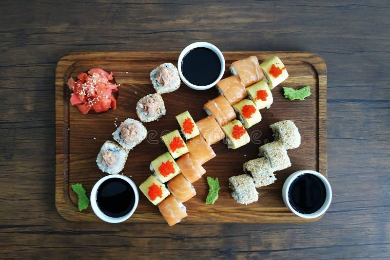 Sushi rolls set served on black stone slate on dark background stock photos