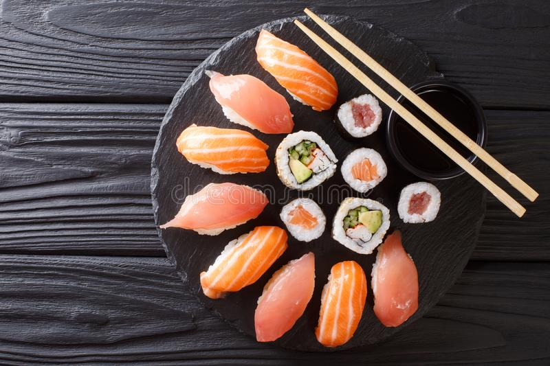 Sushi rolls set served on black stone slate on dark background. stock photography