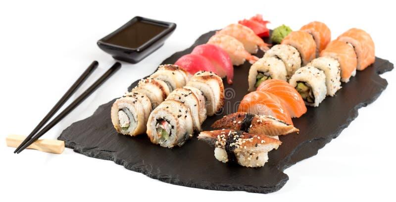 Sushi rolls set served on black stone slate stock photo