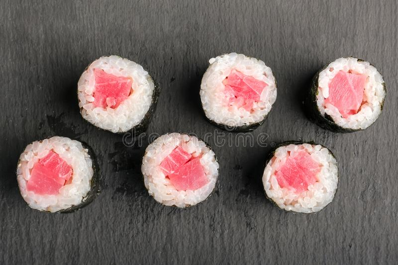 Sushi Rolls with tuna and rice inside wrapped in nori leaf on black slate or stone shale surface. Top view stock photography