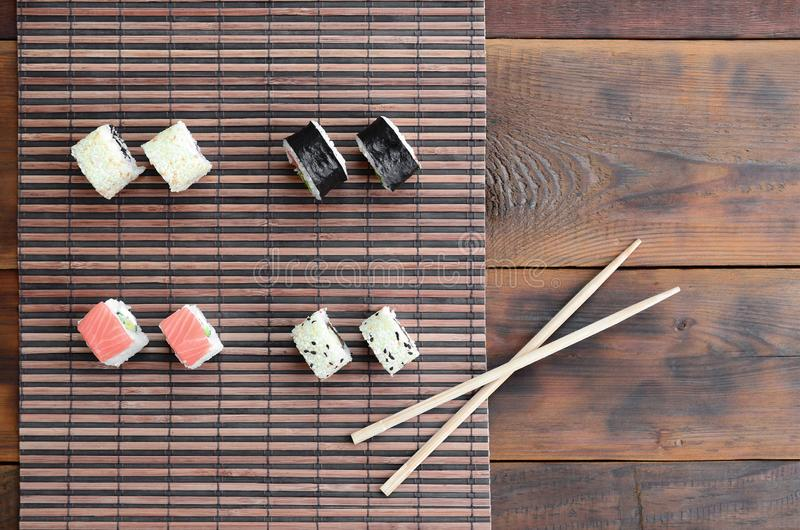 Sushi rolls and wooden chopsticks lie on a bamboo straw serwing mat. Traditional Asian food. Top view royalty free stock images
