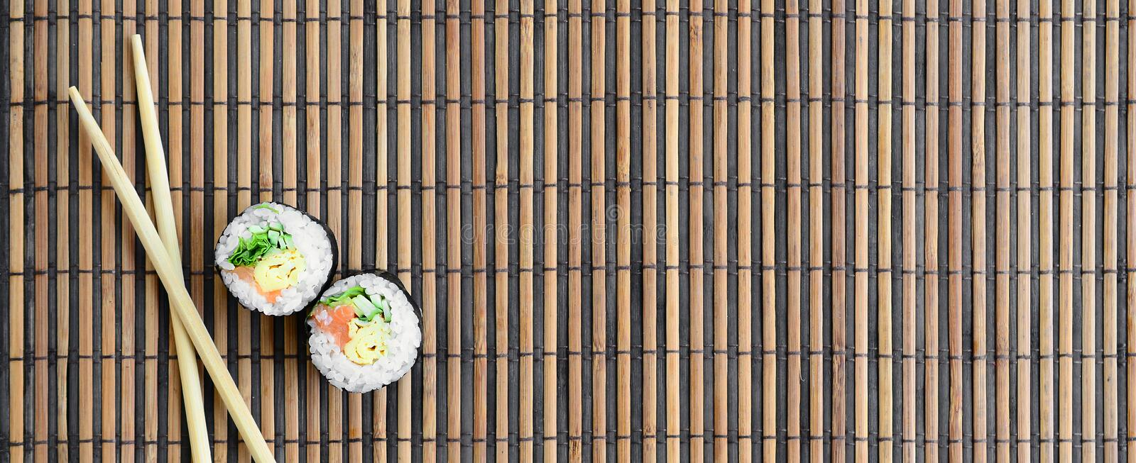 Sushi rolls and wooden chopsticks lie on a bamboo straw serwing mat. Traditional Asian food. Top view. Flat lay minimalism shot. With copy space stock photos