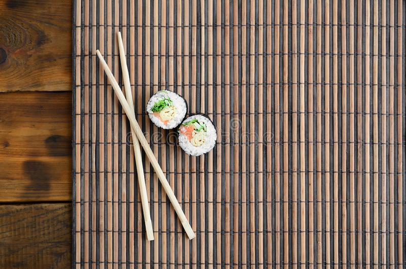 Sushi rolls and wooden chopsticks lie on a bamboo straw serwing mat. Traditional Asian food. Top view. Flat lay minimalism shot. With copy space stock photography