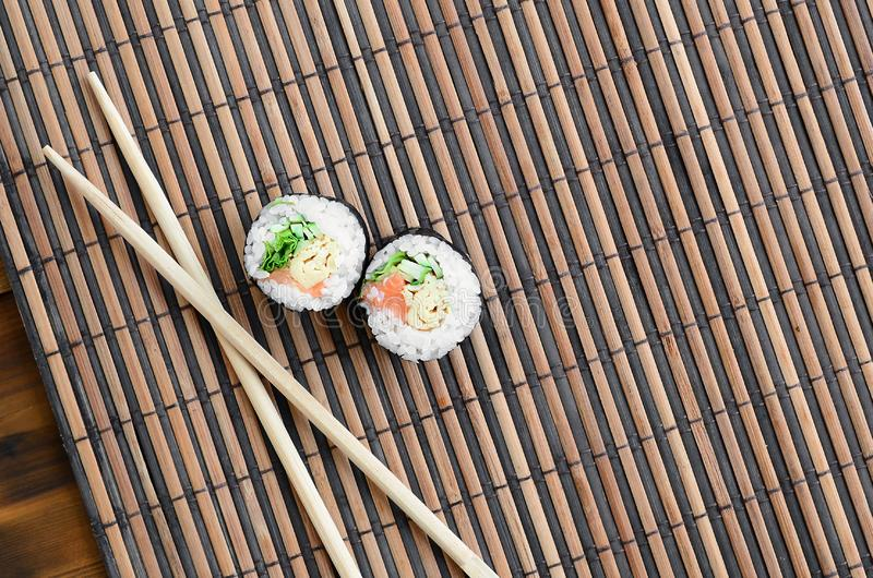 Sushi rolls and wooden chopsticks lie on a bamboo straw serwing mat. Traditional Asian food. Top view. Flat lay minimalism shot royalty free stock image