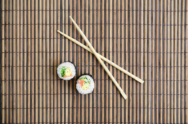 Sushi rolls and wooden chopsticks lie on a bamboo straw serwing mat. Traditional Asian food. Top view. Flat lay minimalism shot. With copy space royalty free stock photo