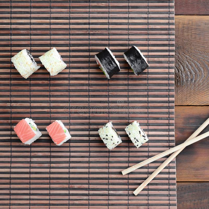 Sushi rolls and wooden chopsticks lie on a bamboo straw serwing mat. Traditional Asian food. Top view royalty free stock photos