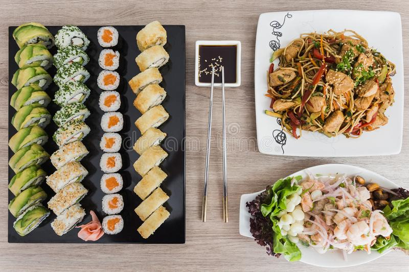 Sushi rolls with yakisoba, ceviche and soy sauce on a wooden table royalty free stock photos