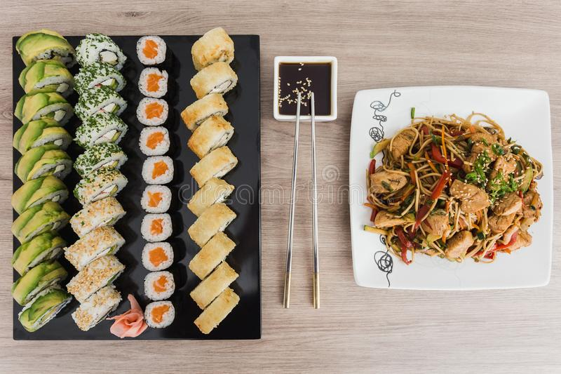 Sushi rolls with yakisoba and soy sauce on a wooden table royalty free stock photography