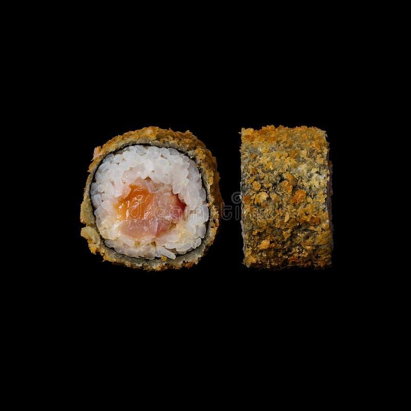 Sushi Rolo com o tempura e o queijo creme dos salmões, isolados no fundo preto foto de stock