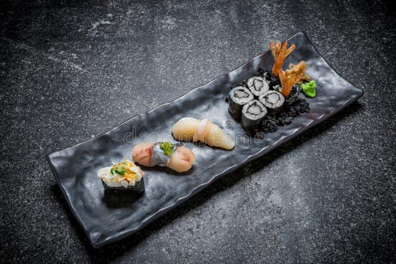Sushi, rolo e hashi japoneses do marisco em uma placa preta foto de stock royalty free