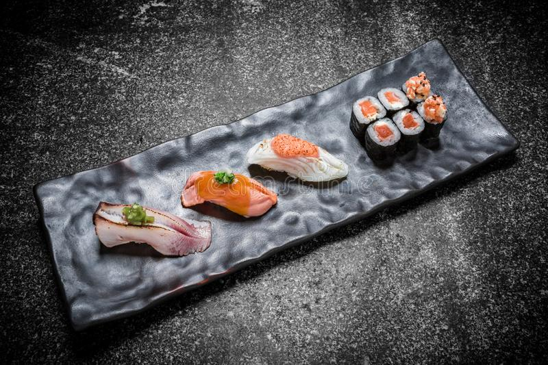 Sushi, rolo e hashi japoneses do marisco em uma placa preta fotos de stock