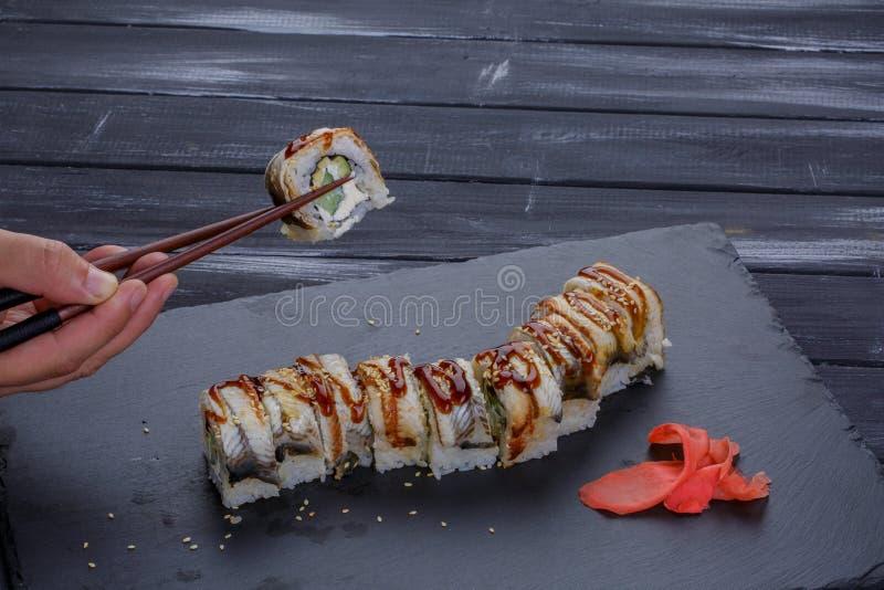 Sushi - rolo em uma placa preta com a mão do homem que guarda hashis sobre o fundo preto fotografia de stock royalty free