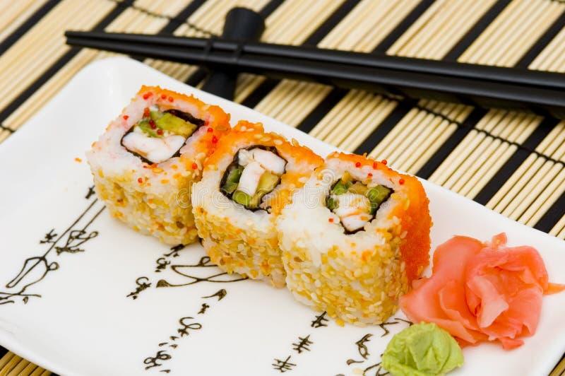 Sushi (rolos) em uma placa fotografia de stock royalty free