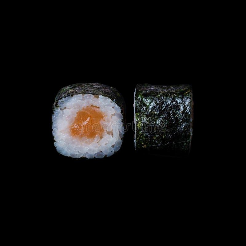 Sushi Rotolo con il salmone in foglia di nori, isolata nel fondo nero fotografie stock