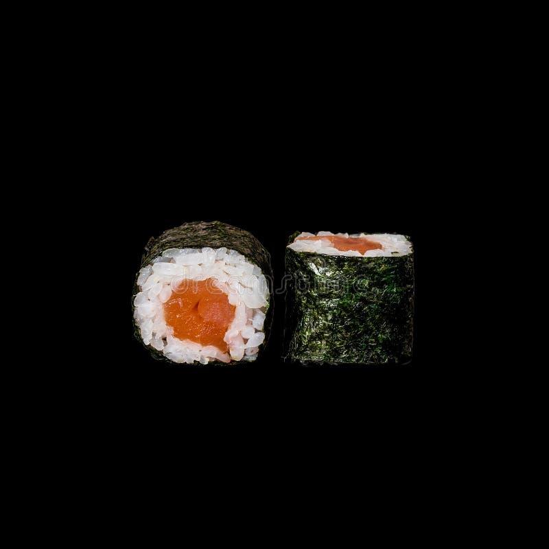Sushi Rotolo con il tonno in foglia di nori, isolata nel fondo nero fotografia stock