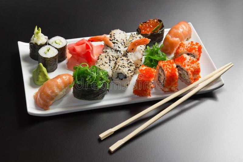 Sushi, roulis et baguettes japonais de fruits de mer photographie stock libre de droits