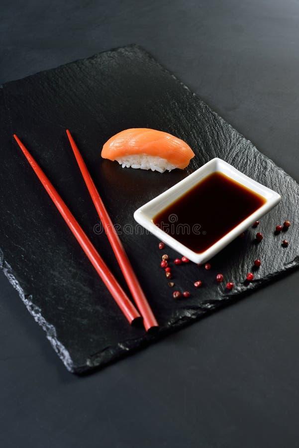 Sushi-saké, sojasås, mörk bakgrund royaltyfria bilder