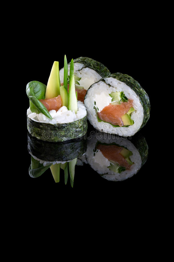 Sushi with salmon and avocado on a black background with reflect stock photos