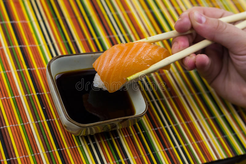 Sushi with salmon on a serving of rice on the background of a bamboo canvas royalty free stock photo