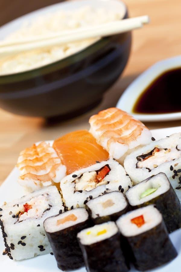 Sushi, salsa di soia, riso e bacchette immagini stock