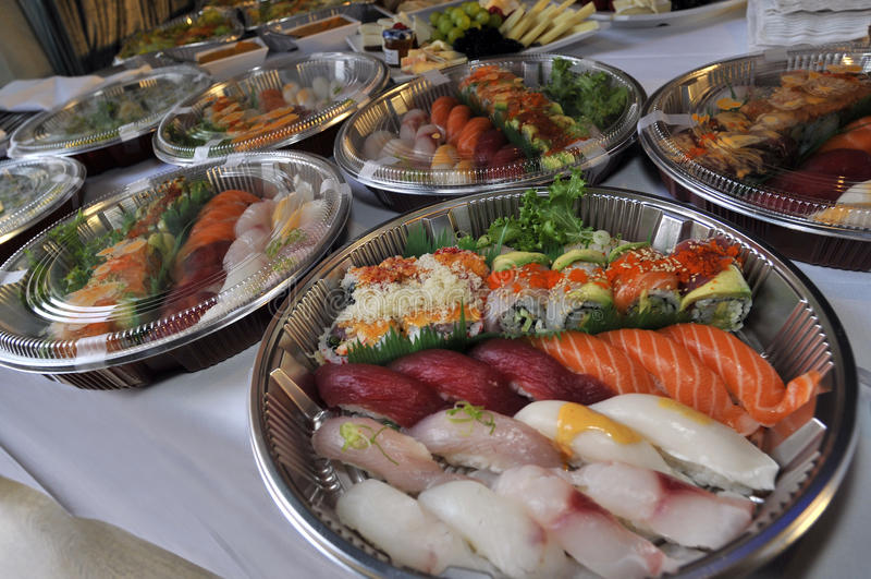 Sushi, sashimi, rolls on trays and cold snacks stock photos