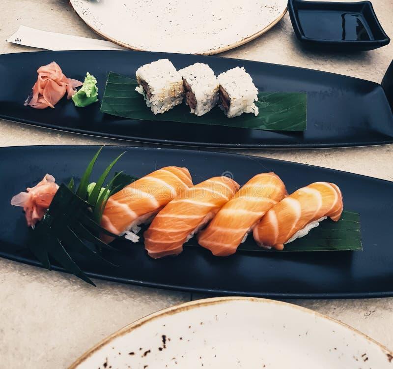 Sushi saumonés de nigiri, à côté des petits pains de maki sur des feuilles dans des plats noirs - cuisine japonaise avec la sauce photos libres de droits
