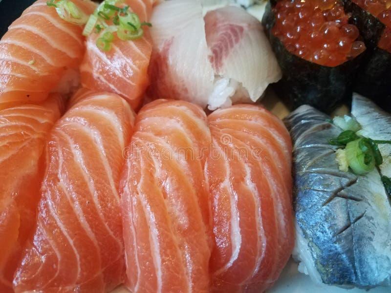 Sushi saumonés oranges et oeufs saumonés avec la ciboulette photographie stock