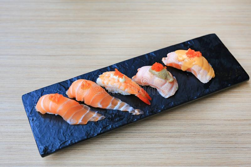Sushi seafood set served on black stone plate on wood table. Japanese cuisine.  stock photo