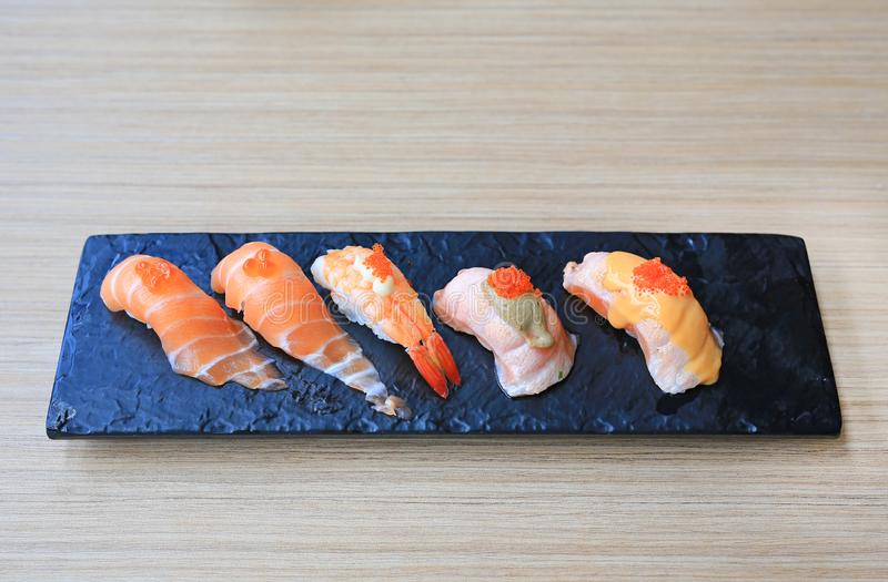 Sushi seafood set served on black stone plate on wood table. Japanese cuisine.  stock photos
