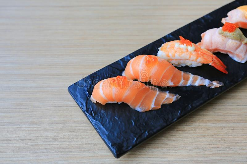 Sushi seafood set served on black stone plate on wood table. Japanese cuisine.  royalty free stock photo