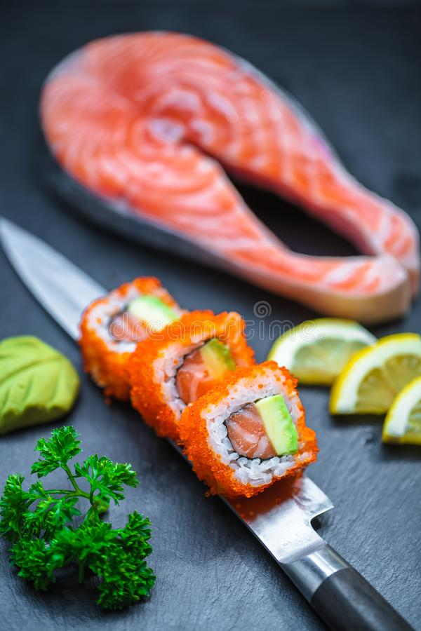 Sushi served on japanese knife on a black slate plate royalty free stock images