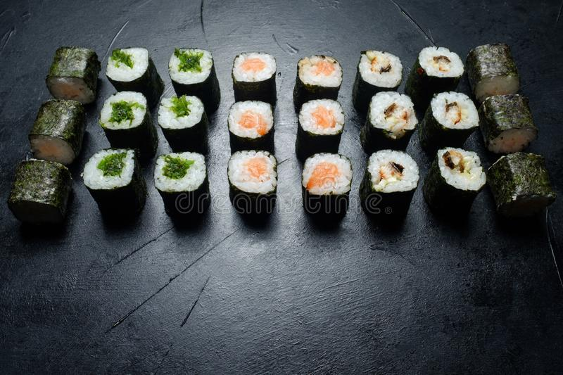 Sushi set assortment food photography art style. Sushi set assortment rolls on dark background. Food photography art style royalty free stock image