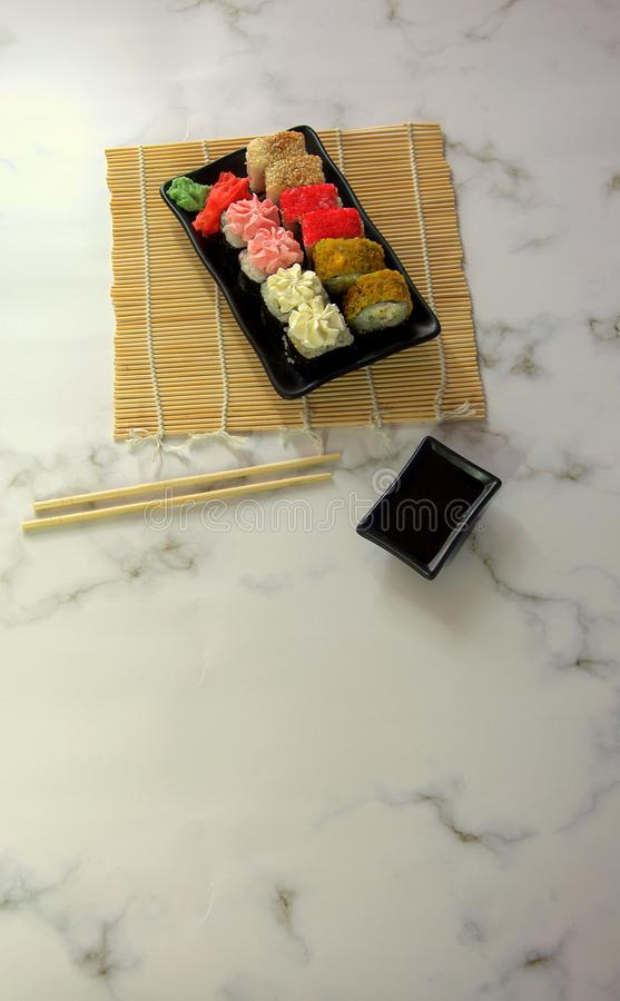 Sushi set on a black flat plate, on a bamboo napkin with chopsticks and a cup with soy sauce royalty free stock photo