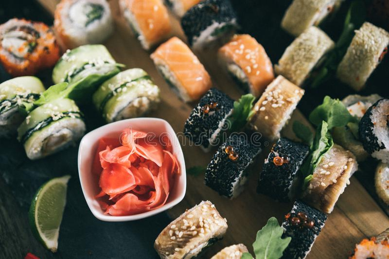 Sushi set food photo. Rolls served on brown wooden and slate plate. Close up and top view of sushi. Vintage toning image stock photo