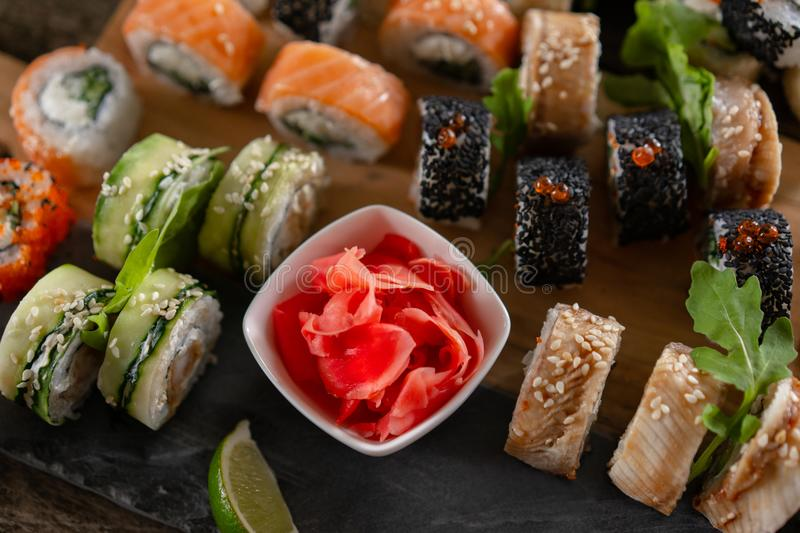 Sushi set food photo. Rolls served on brown wooden and slate plate. Close up view of pickled ginger royalty free stock image