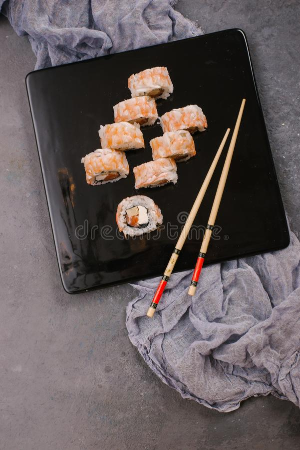 Sushi Set nigiri and sushi rolls in dark ceramic plate with soy sauce, iron teapot and chopsticks over black stone texture royalty free stock image