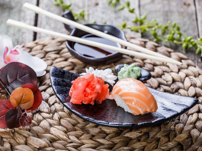 Sushi Set nigiri and sushi rolls decorated with flowers on bamboo background. Japanese cuisine. Selective focus stock photo