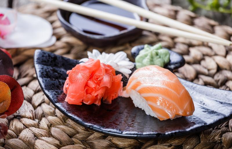 Sushi Set nigiri and sushi rolls decorated with flowers on bamboo background. Japanese cuisine. Selective focus royalty free stock photography