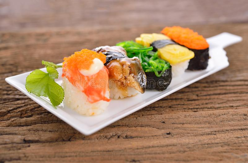Sushi Set nigiri and sashimi served in long white plate on wooden background stock photography